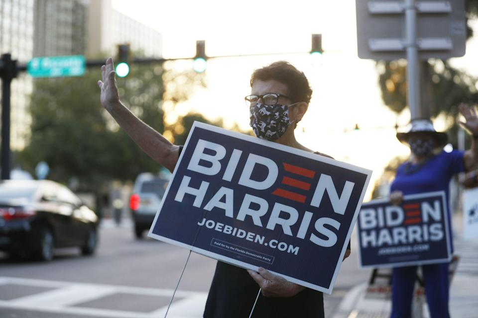 Biden supporters wave at cars passing early voting station in Clearwater, close to the I-4 (Getty)