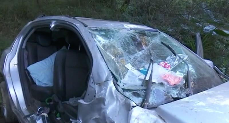 The smashed windshield of the car seen as it sits at the bottom of an embankment off the Princes Highway at Kianga.