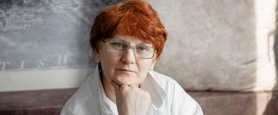 Worried older woman in glasses with red hair.