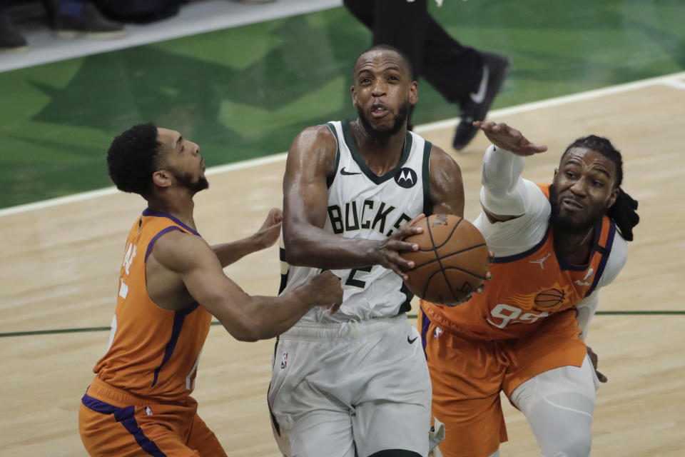 Milwaukee Bucks forward Khris Middleton, center, drives to the basket between Phoenix Suns guard Cameron Payne, left, and forward Jae Crowder, right, during the second half of Game 4 of basketball's NBA Finals Wednesday, July 14, 2021, in Milwaukee. (AP Photo/Aaron Gash)