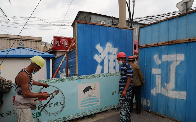 Workers set up a temporary fence outside a residential community after a Covid-19 case was confirmed in a nearby seafood company on July 23, in Dalian - China News Service