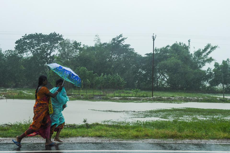 Two women walk with an umbrella under the rain ahead of the expected landfall of cyclone Amphan in Midnapore, West Bengal, on May 20, 2020. (Photo by DIBYANGSHU SARKAR/AFP via Getty Images)