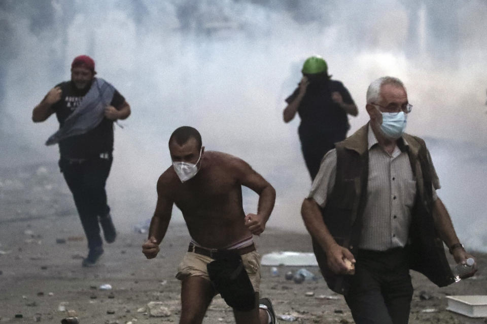 A protestor run away from tear gas during clashes with police as part of a protest against the political elites and the government after this week's deadly explosion at Beirut port which devastated large parts of the capital in Beirut, Lebanon, Saturday, Aug. 8, 2020. (AP Photo/Thibault Camus)