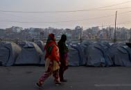 Women walk past rows of tents used by farmers who have gathered to protest against farm laws at Ghaziabad