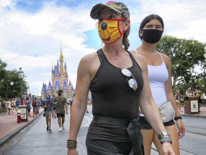 Guests wear masks as required to attend the official reopening day of the Magic Kingdom at Walt Disney World in Lake Buena Vista, Florida: AP