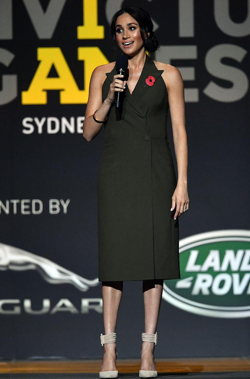 <p>The Duchess gave a speech at the Invictus Games closing ceremony in Australia, wearing a £2,683 khaki halterneck dress by Antonio Berardi and nude Aquazurra heels [Photo: Getty] </p>