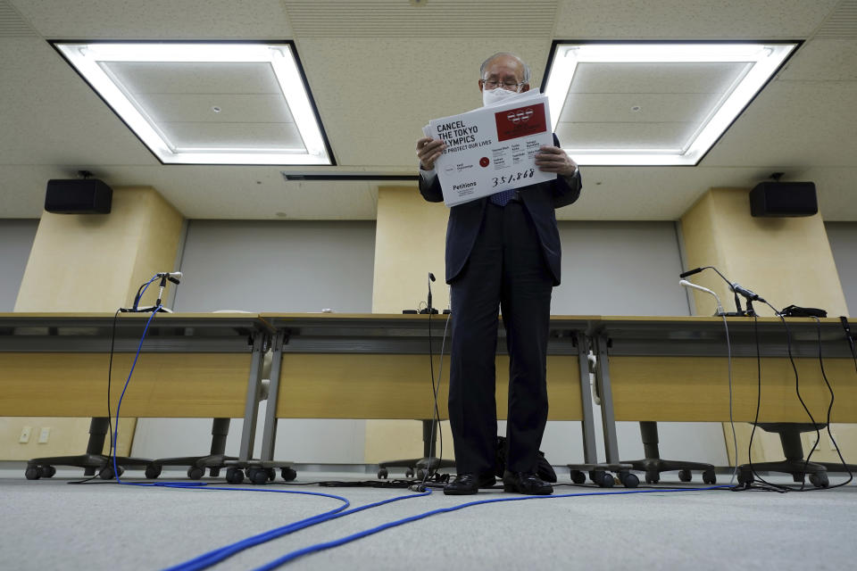 Lawyer Kenji Utsunomiya, a representative of an anti-Olympics group, arranges boards showing the current figure of online petition during a press conference after submitting a petition to the Tokyo government calling for the cancellation of the Tokyo 2020 Olympics and Paralympics. An online petition calling for the Tokyo Olympics to be cancelled has been submitted to the Tokyo government with over 350,000 signatures on Friday morning. The rollout of the petition comes with Tokyo, Osaka and several other areas under a state of emergency with coronavirus infections rising - particularly new variants. (AP Photo/Eugene Hoshiko)