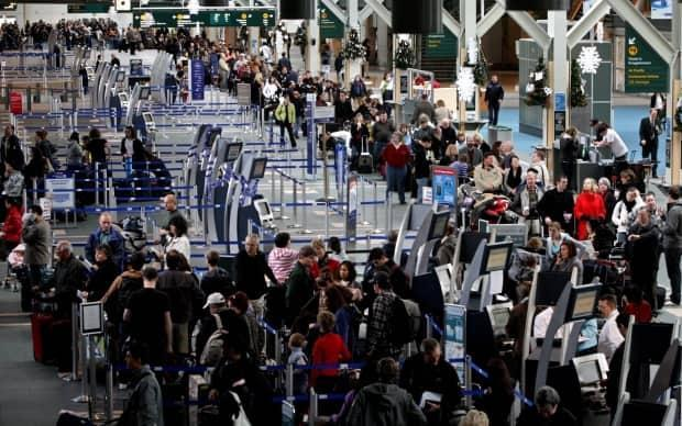 Passengers line up to check in for flights to the United States at Vancouver International Airport on Monday December 28, 2009.