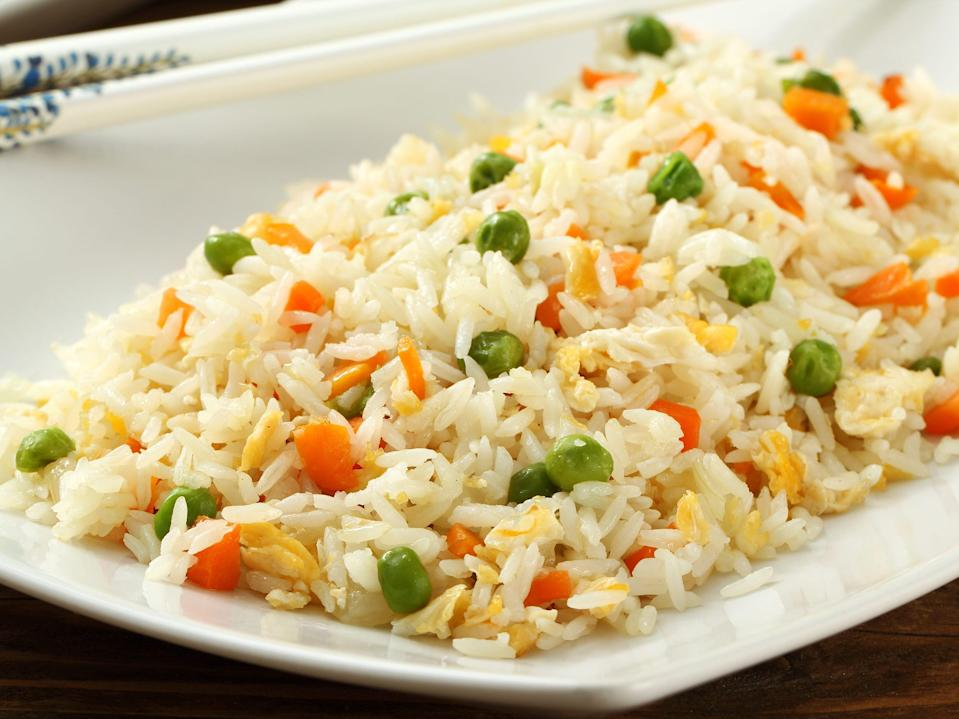 A plate of fried rice with peas, carrots, and eggs.