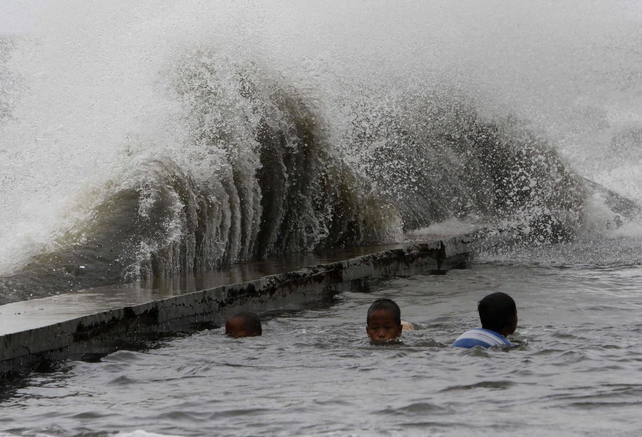 Children swim in a flooded walkway as rough waves crash on concrete banks along the coast of Manila Bay brought by Super Typhoon Usagi in Navotas City, metro Manila September 21, 2013. The year's most powerful typhoon slammed into the Philippines' northernmost islands on Saturday, cutting communication and power lines, triggering landslides and inundating rice fields, officials said. Packing winds of 185 kph (114 mph) near the center and gusts of up to 220 kph, Typhoon Usagi weakened after hitting the Batanes island group, and is moving slowly west-northwest at 19 kph towards southern China, the weather bureau said. REUTERS/Romeo Ranoco (PHILIPPINES - Tags: DISASTER SOCIETY ENVIRONMENT)