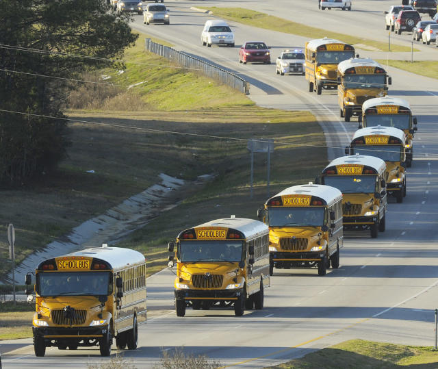 "The funeral procession of slain bus driver Charles ""Chuck"" Poland makes its way down Highway 231 in Ozark, Ala., Sunday Over 60 motorcycles and dozens of school buses join the funeral procession. The Ozark Civic Center was packed with mourners for the funeral. Burial for Poland is in Newton Alabama. (AP Photo/AL.com, Joe Songer)"