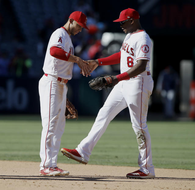 Los Angeles Angels left fielder Justin Upton, right, celebrates with shortstop Andrelton Simmons, after they defeated the Seattle Mariners in a baseball game in Anaheim, Calif., Sunday, Sept. 16, 2018. (AP Photo/Alex Gallardo)