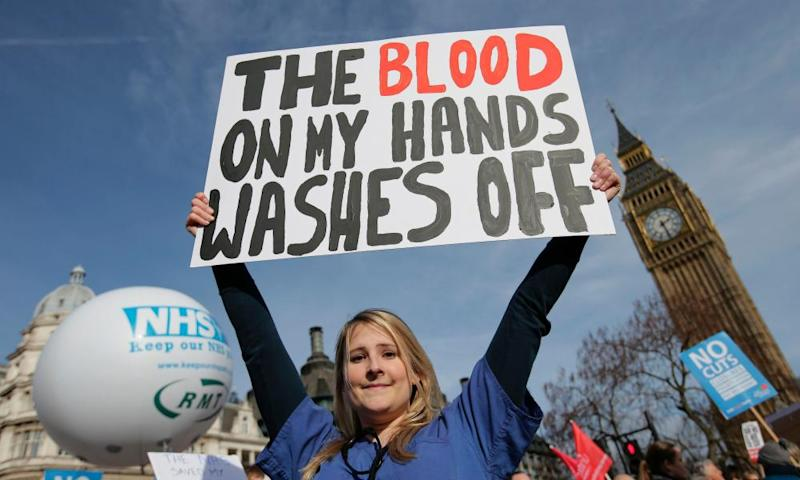 A protester, an NHS doctor, holds a placard up in front of Big Ben that reads: the blood on my hands washes off