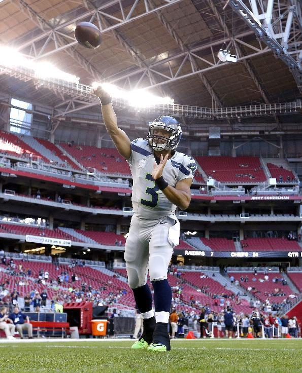 Seattle Seahawks quarterback Russell Wilson warms up for the Seahawks' NFL football game against the Arizona Cardinals, Thursday, Oct. 17, 2013, in Glendale, Ariz. (AP Photo/Ross D. Franklin)