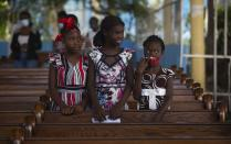 Firls attend Sunday Mass at Sacre-Coeur church, in Port-au-Prince, Sunday, July 11, 2021. four days after President Jovenel Moise was assassinated in his home. (AP Photo/Joseph Odelyn)