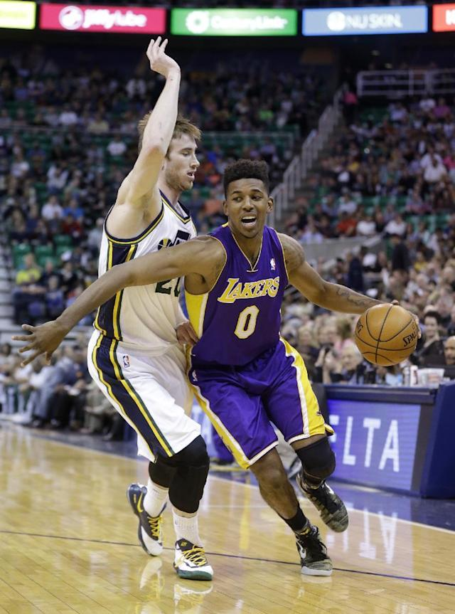 Los Angeles Lakers Nick Young (0) drives around Utah Jazz's Gordon Hayward, left, in the first quarter during an NBA basketball game Monday, April 14, 2014, in Salt Lake City, Utah. (AP Photo/Rick Bowmer)