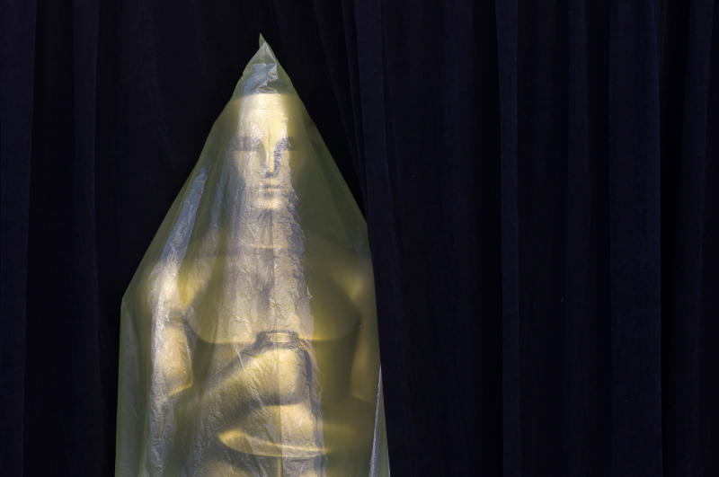 Covered in plastic, an Oscar statue peeks out from a curtain on the red carpet as preparations for the 84th Academy Awards continue in Los Angeles on Friday, Feb. 24, 2012. The Oscars will be held on Sunday. (AP Photo/Amy Sancetta)