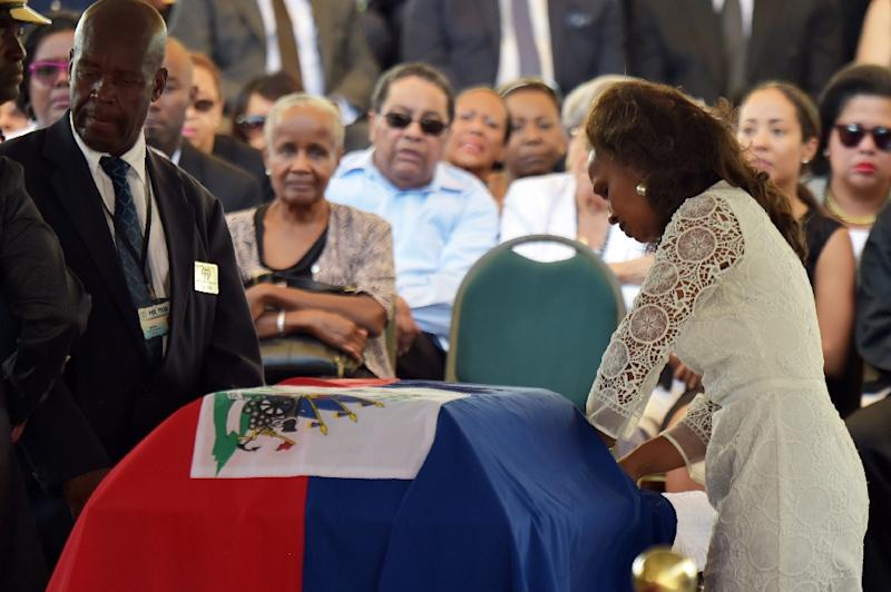 Elisabeth Preval, widow of former President Rene Preval, stands by his casket at the Haitian National Pantheon Museum, in Port-au-Prince, on March 10, 2017 (AFP Photo/HECTOR RETAMAL)