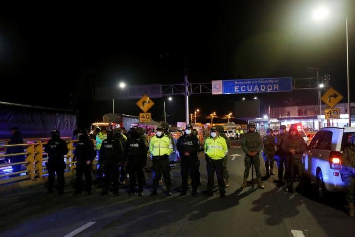 Soldiers and police officers keep watch at Rumichaca International Bridge between Colombia and Ecuador, after Ecuador's government closed its borders to all foreign travelers due to the spread of the coronavirus disease (COVID-19), in Tulcan