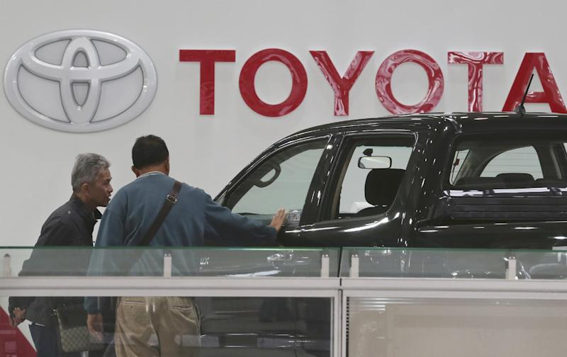 Visitors inspect a car at a Toyota gallery in Tokyo Thursday, May 8, 2014. Toyota's fourth quarter profit dropped slightly despite higher vehicle sales and a weak yen as it spend more on research and development. Toyota Motor Corp. reported Thursday a January-March profit of 297 billion yen ($2.9 billion), down from 313.9 billion yen a year earlier. Quarterly sales rose 12.5 percent to 6.57 trillion yen ($64.5 billion). (AP Photo/Koji Sasahara)