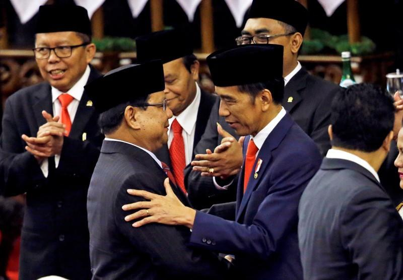 Indonesian President Joko Widodo is congratulated by the Gerindra Party Chairman Prabowo Subianto, who was his former rival in April's election, after his presidential inauguration for the second term, at the House of Representatives building in Jakarta