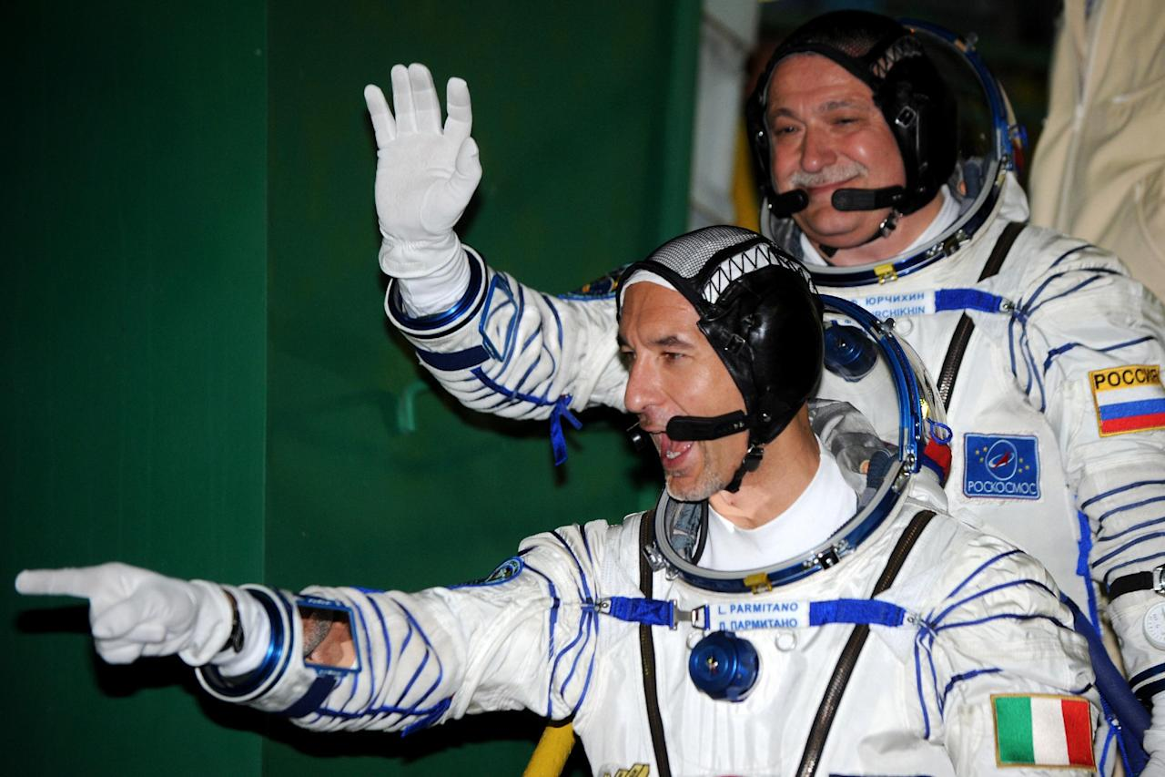Russian cosmonaut Fyodor Yurchikhin, top, and European Space Agency astronaut Luca Parmitano, bottom, crew members of the mission to the International Space Station (ISS), gesture prior to the launch of Soyuz-FG rocket at the Russian leased Baikonur Cosmodrome, Kazakhstan, Wednesday, May 29, 2013. (AP Photo/ Kiril Kudryavtsev, Pool)