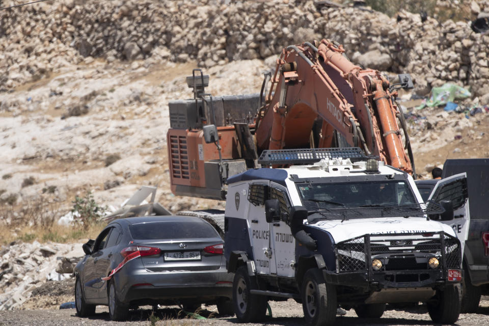 Israeli police tow a car that was said to be used in an attack near Hizmeh Junction in the West Bank, Wednesday, June 16, 2021. The Israeli military on Wednesday shot and killed a Palestinian woman who it said tried to ram her car into a group of soldiers guarding a West Bank construction site. (AP Photo/Maya Alleruzzo)