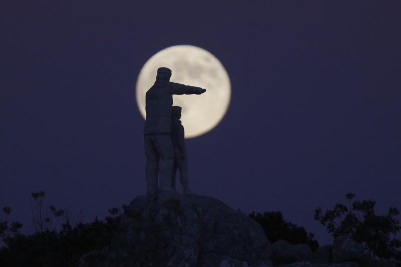 Statue of a man and a boy, is silhouetted against the supermoon as it rises at the Sierra de las Nieves nature park and biosphere reserve between El Burgo and Ronda