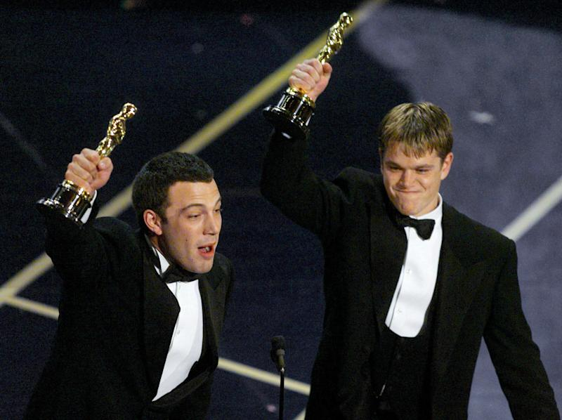 Ben Affleck (L) and Matt Damon hold up their Oscars after winning in the Original Screenplay for their movie Good Will Hunting, March 23. **DIGITAL IMAGE**