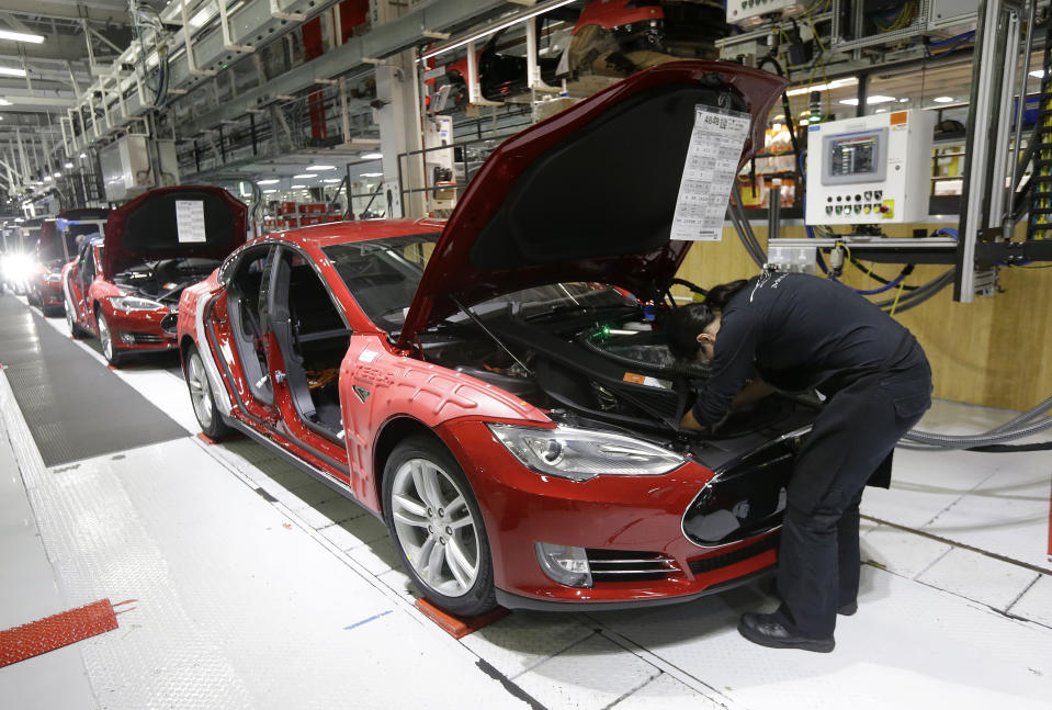 FILE - In this May 14, 2015, file photo, Tesla employees work on a Model S cars in the Tesla factory in Fremont, Calif. The parking lot was full at Tesla's California electric car factory Monday, May 11, 2020, an indication that the company was resuming production in defiance of an order from county health authorities. (AP Photo/Jeff Chiu, File)