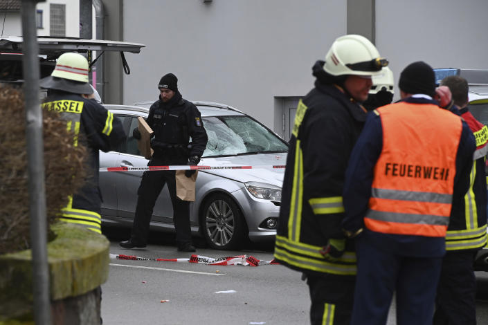 Police and rescue workers stand next to the scene of the accident with a car that is said to have crashed into a carnival parade in Volkmarsen, central Germany. (Uwe Zucchi/dpa via AP)