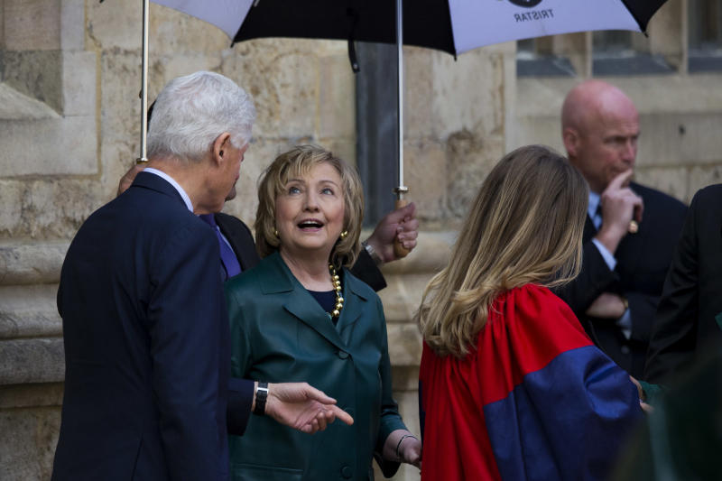 Former U.S. Secretary of State Hillary Rodham Clinton, center, looks up as light rain falls beside her husband former U.S. President Bill Clinton, left, as they wait to pose for a formal photograph with their daughter Chelsea, right, after Chelsea's Oxford University graduation ceremony held at the Sheldonian Theatre in Oxford, England, Saturday, May 10, 2014. Chelsea Clinton received her doctorate degree in international relations on Saturday from the prestigious British university. Her father was a Rhodes scholar at Oxford from 1968 to 1970. The graduation ceremony comes as her mother is considering a potential 2016 presidential campaign. (AP Photo/Matt Dunham)
