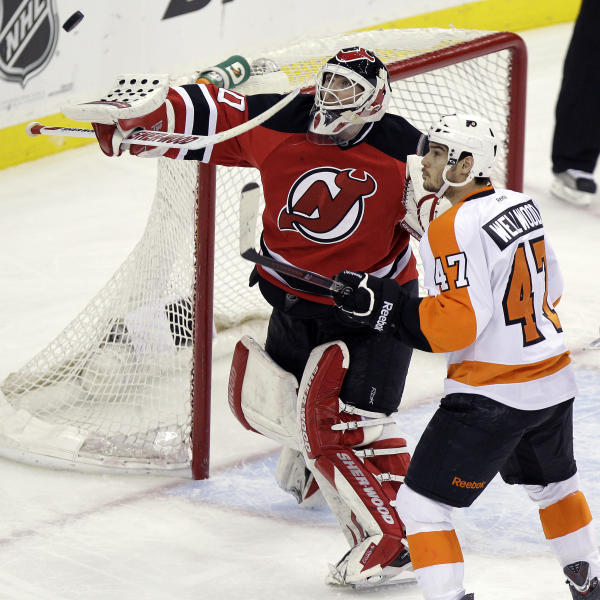 New Jersey Devils goalie Martin Brodeur, left, deflects the puck as Philadelphia Flyers' Eric Wellwood looks on during the third period of Game 4 of a second-round NHL hockey Stanley Cup playoff series, Sunday, May 6, 2012 in Newark, N.J. The Devils won 4-2 and take a 3-1 lead in the series. (AP Photo/Julio Cortez)