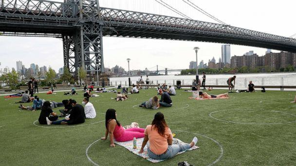 PHOTO: People relax in circles marked on the grass for proper social distancing at Brooklyn's Domino Park during the coronavirus outbreak, May 18, 2020, in New York. (Kathy Willens/AP)
