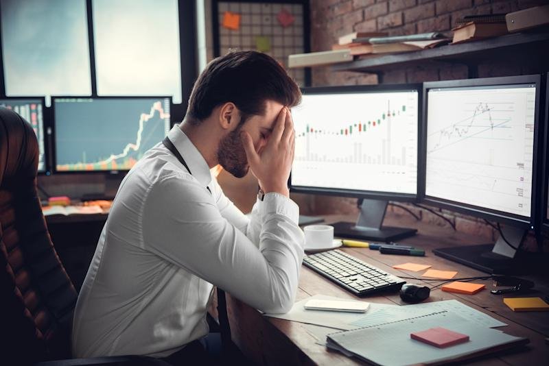 Frustrated depressed trader stressed by stock exchange fall on computer online graphs, sad desperate investor shocked by bankruptcy, financial crisis or money loss, tired businessman having headache