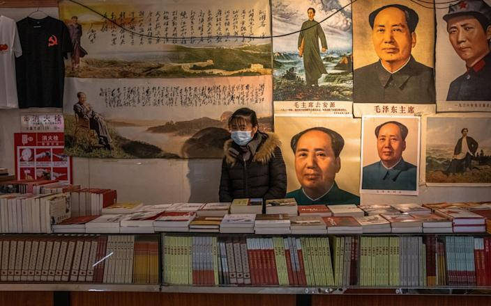 An employee sells books and posters with former Chinese leader Mao Zedong at the Revolution Museum in Jinggangshan, an historically important site for the Chinese Communist revolution - ROMAN PILIPEY/EPA-EFE/Shutterstock