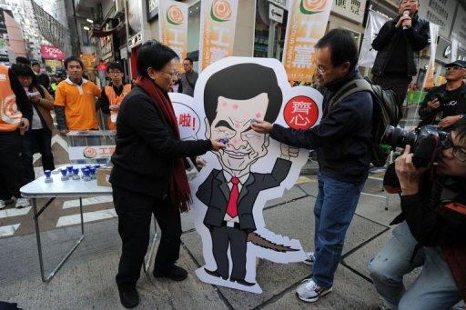 Protestors stamp a placard of the city's leader Leung Chung-ying during a protest, in Hong Kong, on January 1, 2013