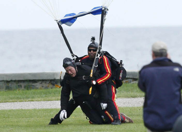 <p>Former President George H.W. Bush, left, strapped to Sgt. 1st Class Mike Elliott, a retired member of the Army's Golden Knights parachute team, lands on the lawn at St. Anne's Episcopal Church after making a tandem parachute jump near Bush's summer home in Kennebunkport, Maine, June 12, 2014. Bush made the jump, his eighth, in celebration of his 90th birthday. (Photo: Robert F. Bukaty/AP) </p>