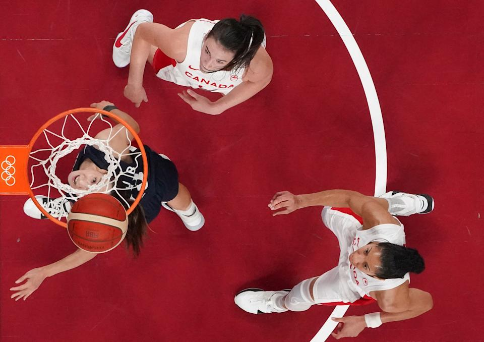 <p>South Korea's Kim Danbi goes to the basket past Canada's Bridget Carleton (top) in the women's preliminary round group A basketball match between South Korea and Canada during the Tokyo 2020 Olympic Games at the Saitama Super Arena in Saitama on July 29, 2021. (Photo by Brian SNYDER / various sources / AFP)</p>