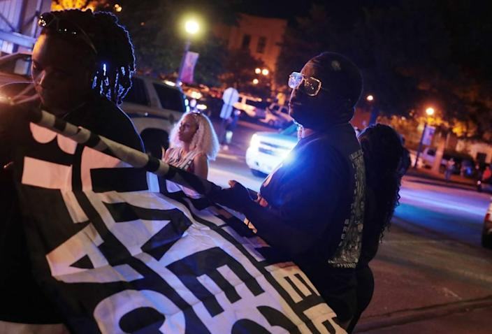 A protester holds a Black Lives Matter flag Thursday during a protest at the Rock Hill Police Department.