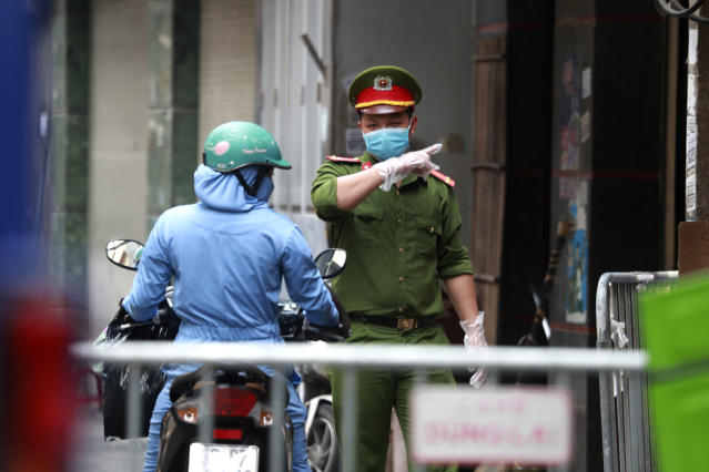 A police officer talks to a woman at the barricaded entrance of an alley where one of its residents is suspected to have COVID-19 in Hanoi, Vietnam on Wednesday, July 29, 2020. Vietnam intensifies protective measures as the number of locally transmissions, starting at a hospital in the popular beach city of Da Nang, keeps increasing since the weekend. (AP Photo/Hau Dinh)