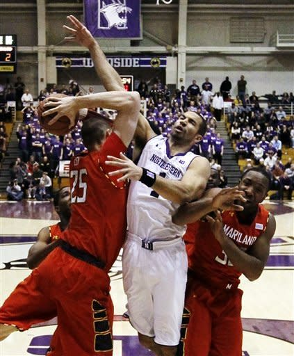 Maryland center Alex Len (25) battles Northwestern's Drew Crawford for a rebound as Maryland forward James Padgett watches during the first half of an NCAA college basketball game, Tuesday, Nov. 27, 2012, in Evanston, Ill. (AP Photo/Charles Rex Arbogast)