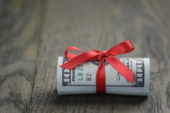 A dollar bill wrapped in a bow.