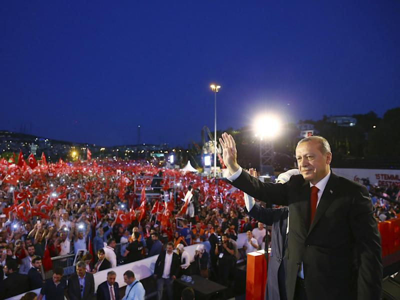 President Erodgan acknowledges supporters at a rally celebrating the anniversary of the failed coup – which he has used to justify sweeping attacks on democracy and human rights: AP