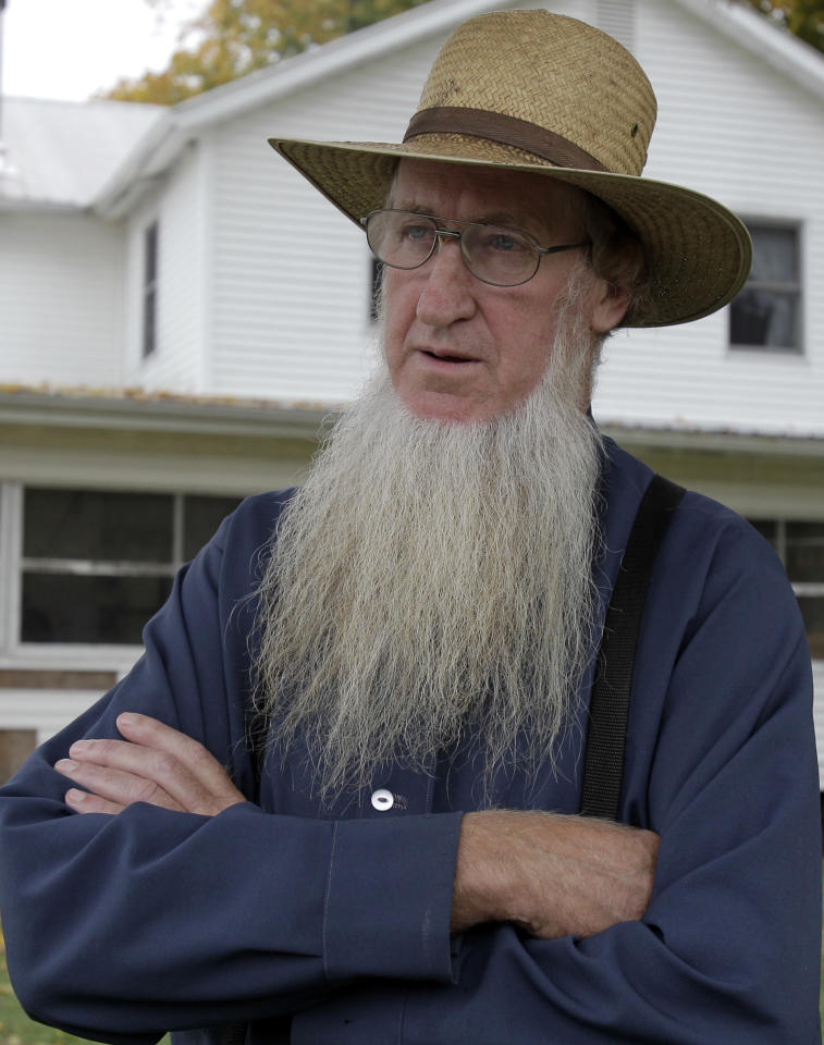 FILE - In this Oct. 10, 2011 file photo, Sam Mullet stands in the front yard of his home in Bergholz, Ohio. The FBI and local sheriff's deputies arrested seven men, including Mullet, reputed leader of a breakaway Amish sect, on federal hate crime charges early Wednesday, Nov. 23, 2011. (AP Photo/Amy Sancetta)