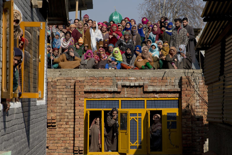 Kashmiri villagers watch the funeral procession of a local rebel Muzamil Ahmed Dar in Rahmoo village south of Srinagar, Indian controlled Kashmir, Saturday, Dec. 29, 2018. Anti-India protests and clashes erupted in disputed Kashmir on Saturday after a gunbattle between militants and government forces killed four rebels, police and residents said. (AP Photo/ Dar Yasin)