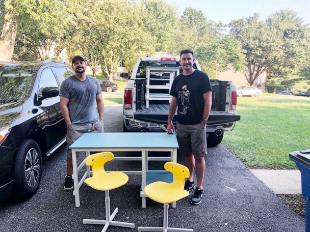 PHOTO:  Members of Desks by Dads stand with one of the more than 30 desks the group has made and distributed for students studying at home during the coronavirus pandemic. (Jessica Berrellez )