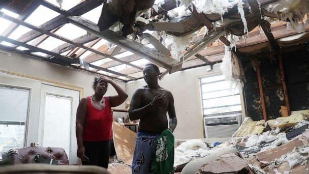 PHOTO: Latasha Myles and Howard Anderson stand in their living room where they were sitting when the roof blew off around 2:30am in Lake Charles, La. , Aug. 27, 2020. (Joe Raedle/Getty Images)