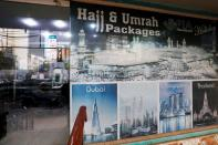 A sign promotes airline's Haj and Umrah packages outside a ticketing office in Karachi