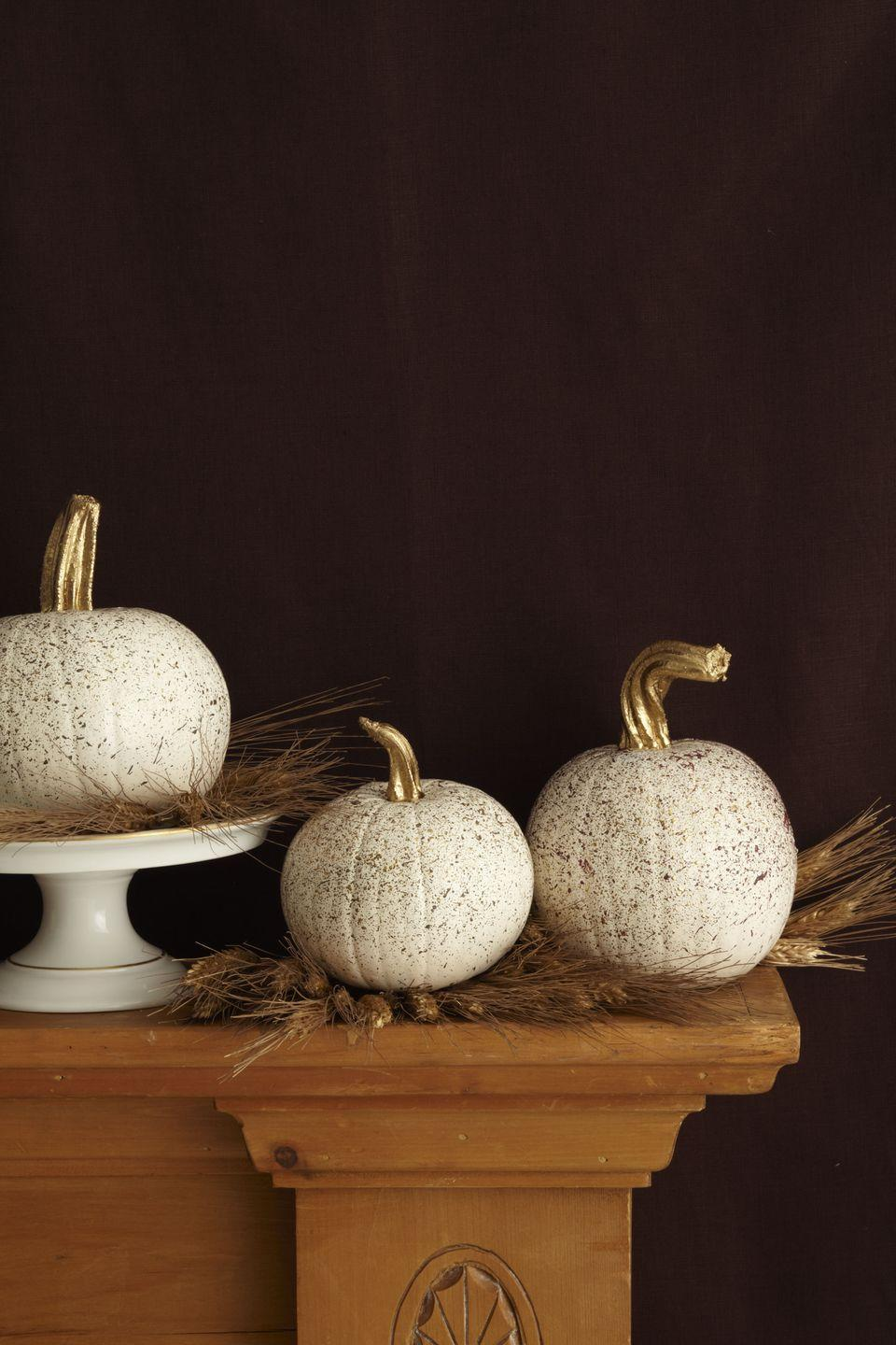 <p>Keep it lowkey with a simple arrangement of white pumpkins splattered with gold paint, arrange atop wheat on your mantel. Paint the stems gold too, for an extra sparkling touch. </p>